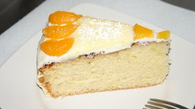 Sponge cake decorated with peach and tangerines. royalty free stock images
