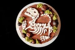 Sponge cake with eatable dinosaur skeleton. Sponge cake with funny eatable dinosaur skeleton from sugar paste in black background stock photos