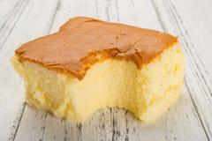 Sponge cake on white wood background. With a bite Stock Photo