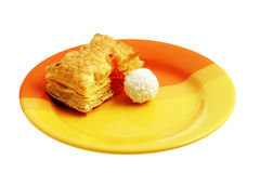 Sponge and candy on colored plate Royalty Free Stock Image