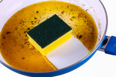 Sponge in clean a frying pan Royalty Free Stock Image