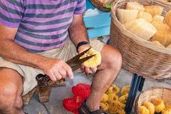 Sponge Cutter trims sea sponge tampon in street shop on Symi island Rhodes, Greece stock images
