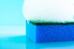 Sponge with foam and bubbles, close-up, texture, light blue background. Bright photo. royalty free stock photos