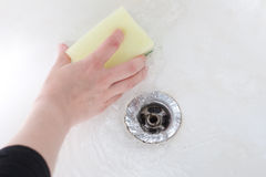 Sponge in hand. Washing the bath Royalty Free Stock Image
