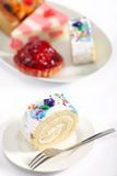 Sponge roll and plate of cakes Stock Photos