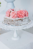 Sponge wedding cake decorated with fresh flowers on a white pedestal. Wedding cake on a white pedestal decorated with fresh flowers: Carnation Lily Rose Royalty Free Stock Image