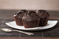 Spongecake or muffin with chocolate sauce. On wooden beckground Royalty Free Stock Image