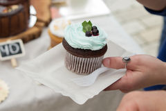 Spongecake or muffin with cream. In hand Royalty Free Stock Image