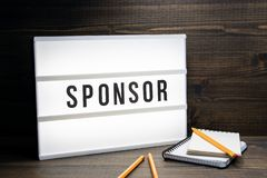 Sponsor concept. Text in lightbox. Wooden office table stock photo