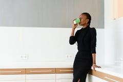 Spontaan beeld van een onderneemster het drinken koffie terwijl het werken op licht kantoor Royalty-vrije Stock Foto