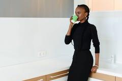 Spontaan beeld van een onderneemster het drinken koffie terwijl het werken op licht kantoor Stock Foto's