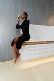 Spontaan beeld van een onderneemster het drinken koffie terwijl het zitten op bureau op licht kantoor Royalty-vrije Stock Foto's
