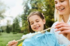 Spontaan beeld van gelukkig meisje die pret hebben en gesponnen suiker met haar moeder in het park eten royalty-vrije stock fotografie