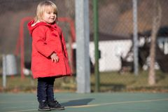 Spontaan jong babymeisje die de winterkleren lachen dragen openlucht in zonnige dag Stock Foto's
