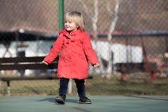 Spontaan jong babymeisje die de winterkleren lachen dragen openlucht in zonnige dag Royalty-vrije Stock Foto's