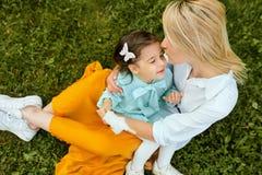 Spontaan in openlucht beeld die van mooie moeder en met haar dochter spelen knuffelen, van de tijd samen genieten royalty-vrije stock foto's