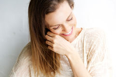 Spontaan portret van een vrouw die tegen witte achtergrond lachen stock afbeeldingen