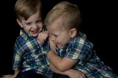 Spontaan portret van twee het jonge jongens spelen die elkaar worstelen Royalty-vrije Stock Foto