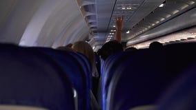Spontaan schot tussen zetels van passagiers die binnen vliegtuig zitten terwijl het reizen stock videobeelden