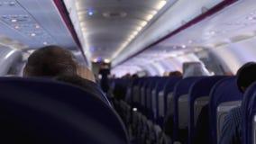 Spontaan schot tussen zetels van passagiers die binnen vliegtuig zitten terwijl het reizen stock video