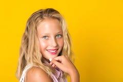 Spontaan tienermeisje met perfecte tanden en glimlach die aan camera kijken Gezichtsportret van mooi meisje 12 jaar op gele achte stock foto's