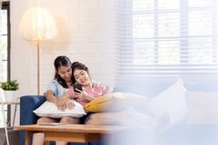 Spontaan van jong aantrekkelijk gelukkig Aziatisch lesbisch paar geniet van de zitting van het vakantieweekend op laag in woonkam stock foto's