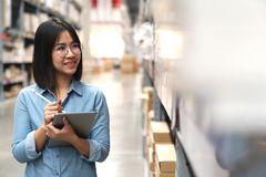 Spontaan van jonge aantrekkelijke Aziatische vrouw, auditor of stagiair slaat het personeel die in pakhuis werken langs het telle stock afbeelding