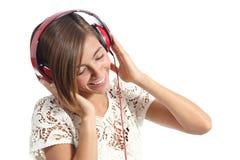 Spontane gelukkige vrouw die de muziek van rode hoofdtelefoons voelen Stock Foto's