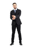 Spontaneous laughing man in suit looking at camera adjusting sleeves Stock Images