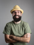 Spontaneously hard laughing bearded man wearing straw hat looking at camera. Stock Image