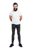 Spontaneously laughing bearded man with hands on back in white t-shirt Stock Photography