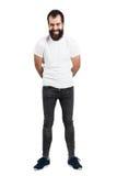 Spontanicznie śmiać się brodatego mężczyzna z rękami na plecy w białej koszulce Fotografia Stock