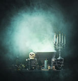 Spookey Halloween composition with a skull in a dungeon. Halloween background with a lot of different witchcraft tools: scull, candles, book, poison and smoke Stock Image