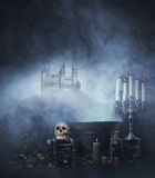 Spookey Halloween composition with a skull in a dungeon. Halloween background with a lot of different witchcraft tools: scull, candles, book, poison and smoke Royalty Free Stock Image