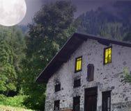 Spookhuis in het hout, met maan in de hemel stock afbeelding