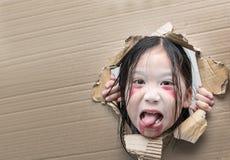 Spookjong geitje die door gat op karton kijken Royalty-vrije Stock Fotografie