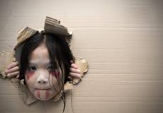 Spookjong geitje die door gat op karton kijken Royalty-vrije Stock Afbeeldingen