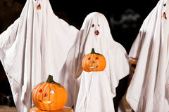 Spooks at Halloween - focus on pumpkin. Three very, very scary spooks - kids dressed as ghosts - on Halloween or for carnival or a costume party, FOCUS IS ON Stock Photo