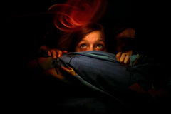 Spooky. A teenage girl covering her face with the bedsheets to protect herself from a ghost Royalty Free Stock Images