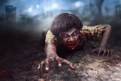 Spooky and bloody asian zombie man in clothes crawling. On the city stock photo