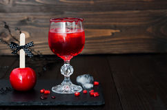 Spooky bloody cocktail and red caramel apple. Traditional dessert and drink recipe for Halloween party. Selective focus. Copy spac Stock Photos