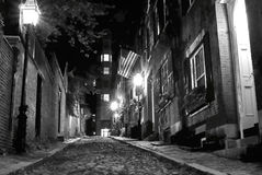 Spooky boston. Black and white night image of an old 19th Century cobble stone road in Boston Massachusetts, lit only by the gas lamps revealing the shuttered Royalty Free Stock Photos