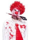 Spooky Clown Holding Bloody Saw In Mouth On White. Isolated Creepy Clown Wearing Bright Red Wig Holding Bloody Saw In Mouth In A Depiction Of A Horror Slasher Royalty Free Stock Image