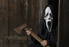 Spooky creature ready to attack with ax stock image