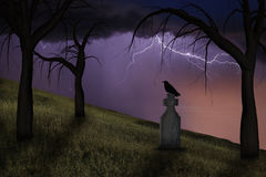Spooky crow on a headstone in a graveyard. Under stormy skies Stock Image