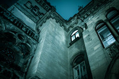 Spooky dark castle house hallowen. Bottom view with bright windo. W Royalty Free Stock Images