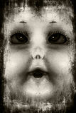 Spooky doll. A spooky and disturbing image of a doll on a grunge and old photo effect Stock Images