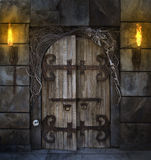 Spooky Door. Spooky dungeon door flanked with two flaming torches and decorated with twigs and skeleton bones Stock Photography