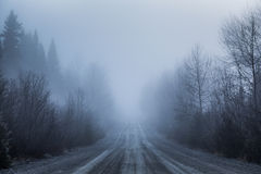 Spooky Fog and Bad Visibility on a Rural Road in Forest. During Winter Stock Photos