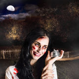 Spooky girl with silver service bell in graveyard. Creepy deceased zombie woman holding silver service bell in a spooky graveyard location in a depiction of Stock Photos